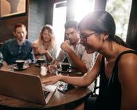 Groupe d'amis en café observant quelque chose en ligne sur l'ordinateur portable Photos stock