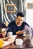 Groupe d'amis en café utilisant des téléphones portables Images libres de droits