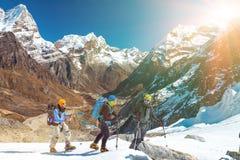 Groupe d'amis en montagnes traversant le glacier vers Soleil Levant Photographie stock