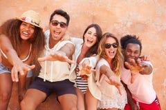 Groupe d'amis en vacances posant ensemble par le mur Image stock