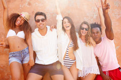 Groupe d'amis en vacances posant ensemble par le mur Photos libres de droits