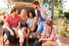 Groupe d'amis en voyage se reposant dans le tronc de la voiture Images stock