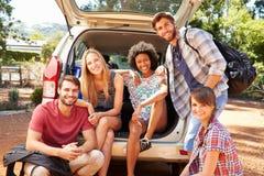 Groupe d'amis en voyage se reposant dans le tronc de la voiture Image stock