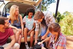 Groupe d'amis en voyage se reposant dans le tronc de la voiture Photos libres de droits