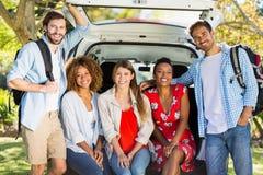 Groupe d'amis en voyage se reposant dans le tronc de la voiture Photographie stock