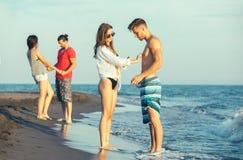 Groupe d'amis ensemble sur la plage Photos libres de droits