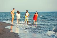 Groupe d'amis ensemble sur la plage Images stock