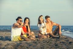 Groupe d'amis ensemble sur la plage Photographie stock libre de droits
