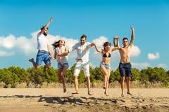 Groupe d'amis ensemble sur la plage ayant l'amusement Photographie stock
