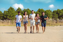 Groupe d'amis ensemble sur la plage ayant l'amusement Image libre de droits