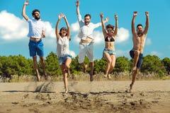 Groupe d'amis ensemble sur la plage ayant l'amusement Image stock