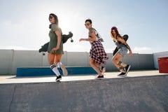 Groupe d'amis féminins appréciant au parc de patin Photo stock