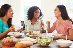 Groupe d'amis féminins appréciant le repas à la maison Photo stock