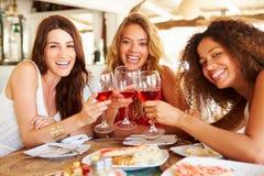Groupe d'amis féminins appréciant le repas dans le restaurant extérieur Photos libres de droits