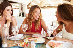 Groupe d'amis féminins appréciant le repas dans le restaurant extérieur Image stock