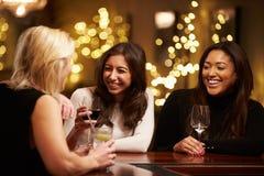 Groupe d'amis féminins appréciant même des boissons dans la barre Photographie stock libre de droits