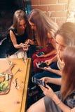 Groupe d'amis féminins assez jeunes mangeant ensemble en café utilisant des smartphones Photographie stock