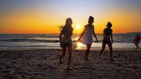 Groupe d'amis féminins ayant l'amusement fonctionnant en bas de la plage au coucher du soleil Photo stock