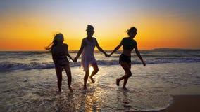 Groupe d'amis féminins ayant l'amusement fonctionnant en bas de la plage au coucher du soleil Images stock
