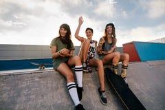 Groupe d'amis féminins détendant au parc de patin Photos stock