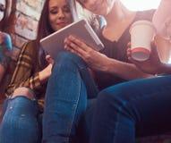 Groupe d'amis féminins dans des vêtements sport discutant tout en regardant quelque chose sur un comprimé numérique dans une cham Photo libre de droits