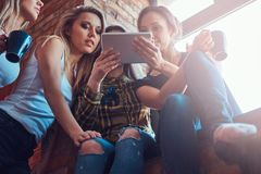 Groupe d'amis féminins dans des vêtements sport discutant tout en regardant quelque chose sur un comprimé numérique dans une cham Images stock