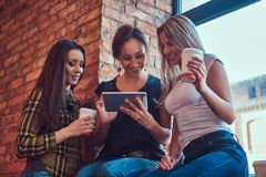 Groupe d'amis féminins dans des vêtements sport discutant tout en regardant quelque chose sur un comprimé numérique dans une cham Photo stock