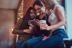 Groupe d'amis féminins dans des vêtements sport discutant tout en regardant quelque chose sur un comprimé numérique dans une cham Photos stock