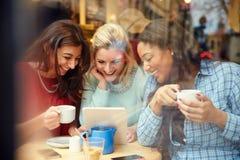 Groupe d'amis féminins dans le ½ de ¿ de Cafï utilisant des dispositifs de Digital Photo libre de droits