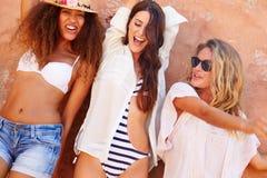 Groupe d'amis féminins en vacances posant ensemble par le mur Images stock