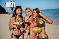 Groupe d'amis féminins prenant le selfie sur le bord de mer Image stock