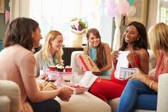 Groupe d'amis féminins se réunissant pour la fête de naissance à la maison Photos stock