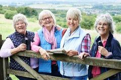 Groupe d'amis féminins supérieurs trimardant dans la campagne Image libre de droits