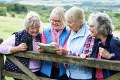 Groupe d'amis féminins supérieurs trimardant dans la campagne Photo stock