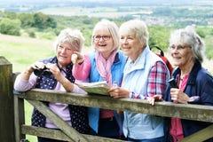 Groupe d'amis féminins supérieurs trimardant dans la campagne Photographie stock