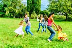 Groupe d'amis féminins tenant des mains et jouant en parc Photo stock