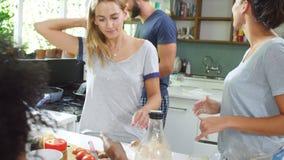 Groupe d'amis faisant cuire le petit déjeuner dans la cuisine ensemble banque de vidéos
