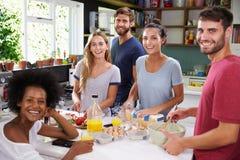 Groupe d'amis faisant cuire le petit déjeuner dans la cuisine ensemble Images stock