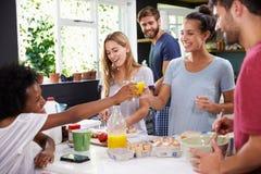 Groupe d'amis faisant cuire le petit déjeuner dans la cuisine ensemble Image libre de droits