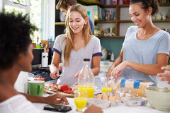 Groupe d'amis faisant cuire le petit déjeuner dans la cuisine ensemble Images libres de droits