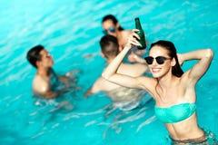 Groupe d'amis faisant la fête dans la piscine Photos stock