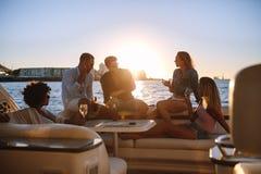 Groupe d'amis faisant la fête sur le yacht au coucher du soleil Photographie stock libre de droits