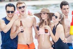 Groupe d'amis faisant la partie dans la piscine et buvant la boisson Image libre de droits