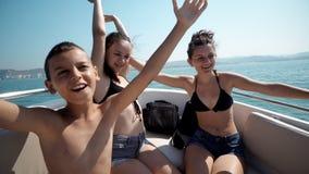 Groupe d'amis faisant la partie sur le bateau Image libre de droits