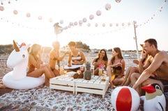 Groupe d'amis faisant la partie sur la plage au temps de coucher du soleil Photo libre de droits