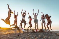 Groupe d'amis faisant la partie sur la plage au temps de coucher du soleil Image stock