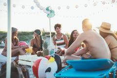 Groupe d'amis faisant la partie sur la plage au temps de coucher du soleil Photos libres de droits