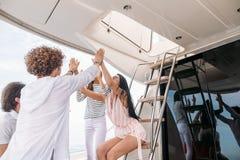Groupe d'amis faisant la partie sur un yacht, ayant une partie de fantaisie sur un bateau de luxe Image stock