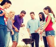 Groupe d'amis faisant le barbecue sur la plage Photos libres de droits