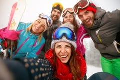 Groupe d'amis faisant le selfie et ayant l'amusement sur la neige Photo stock